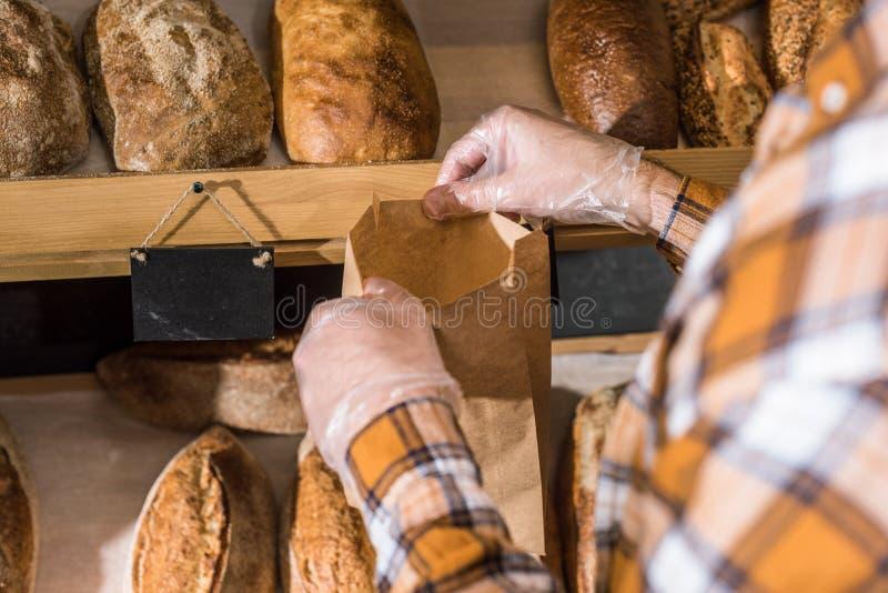 bebouwde mening van mannelijke handen die brood zetten royalty-vrije stock foto's