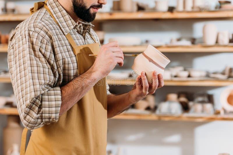 bebouwde mening van mannelijke pottenbakker die ceramische dishware met borstel schilderen royalty-vrije stock afbeelding