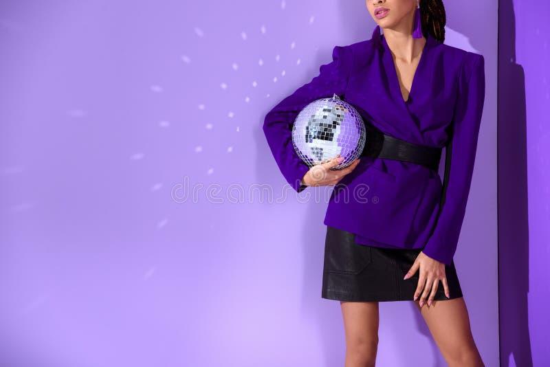bebouwde mening van meisje het stellen in in purper jasje en het houden van discobal bij ultraviolet royalty-vrije stock fotografie