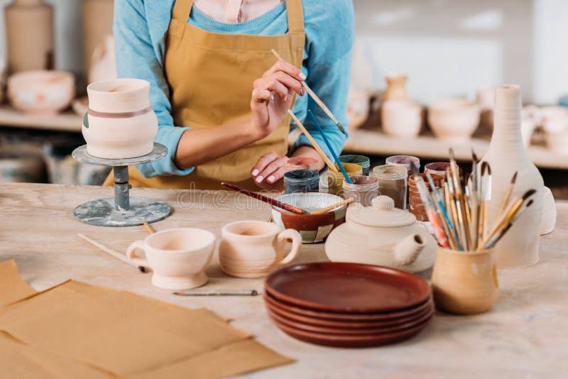 bebouwde mening van pottenbakker in schort die ceramische dishware schilderen royalty-vrije stock foto's