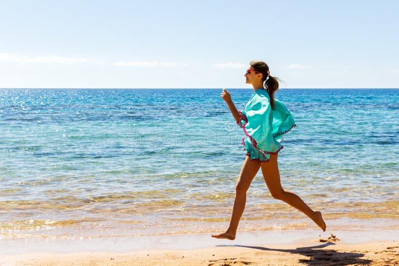 bech的连续妇女 跑步在海滩的室外锻炼期间的母赛跑者 免版税库存图片