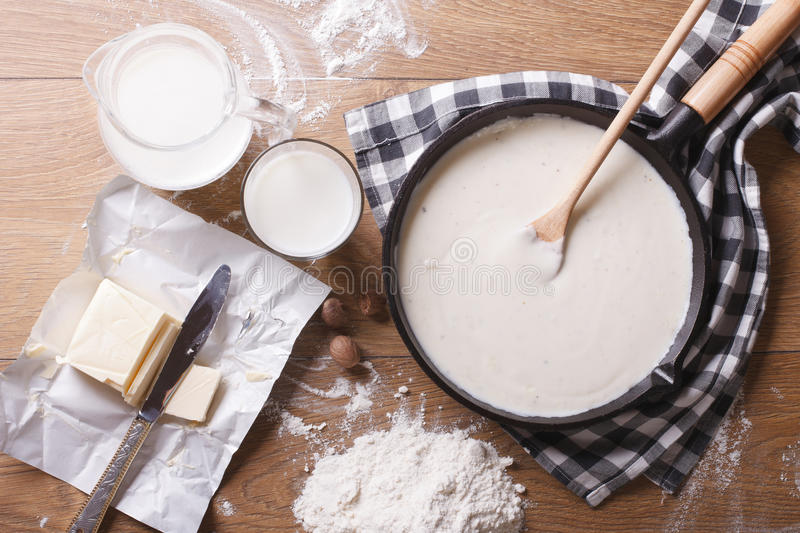 Bechamel sauce in a pan and ingredients horizontal top view royalty free stock photos