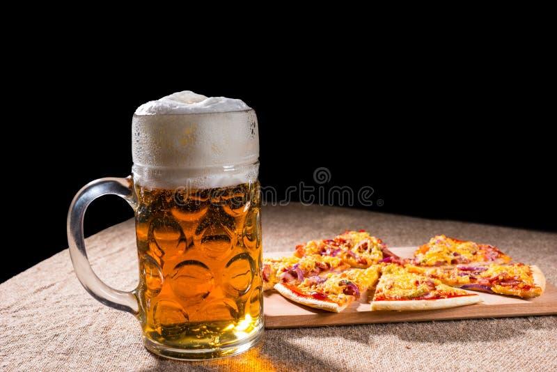 Becher Bier und Scheiben der Pizza auf Schneidebrett stockbild