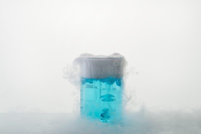 Becher con liquido blu sulla tavola fotografia stock
