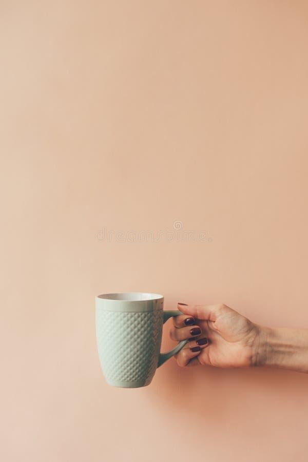 Becher in der Hand auf einem leeren Hintergrund lizenzfreie stockfotografie