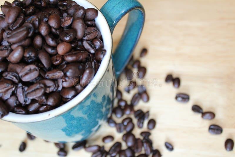 Becher, der mit Kaffeebohnen überläuft lizenzfreie stockfotografie