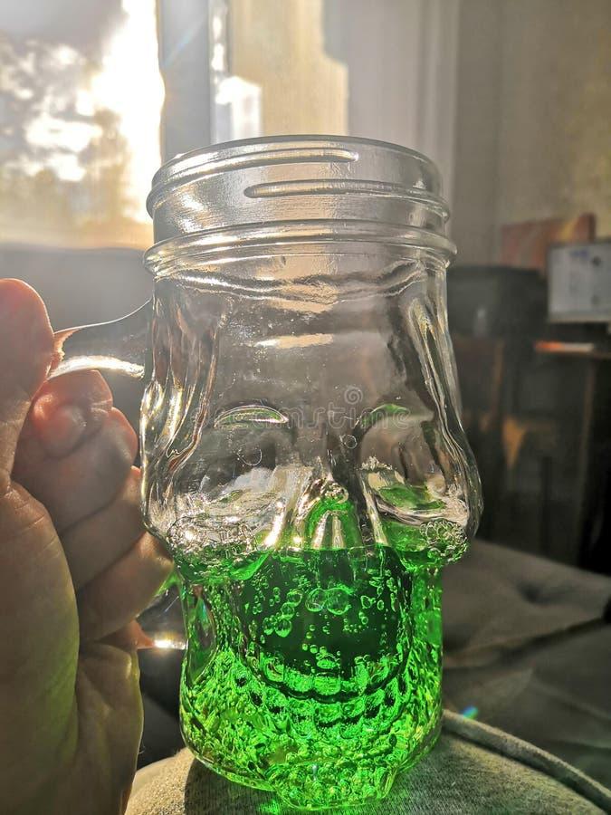 Becher in Form eines Schädels mit einem grünen Getränk lizenzfreies stockfoto