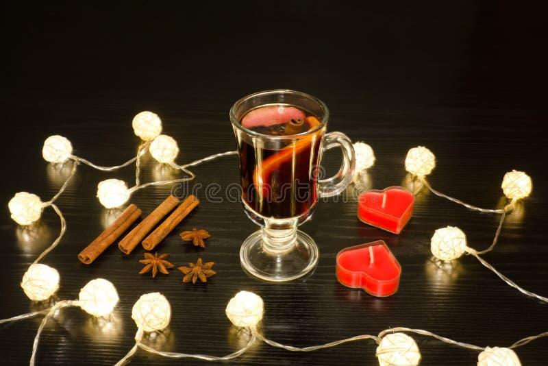 Becher Glühwein mit Gewürzen, Kerzen in Form eines Herzens lizenzfreies stockfoto