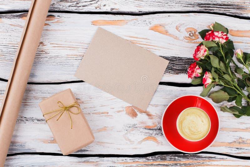 Becher Kaffee, Blumen, Geschenk und leeres Papier für Ihren Text stockbild