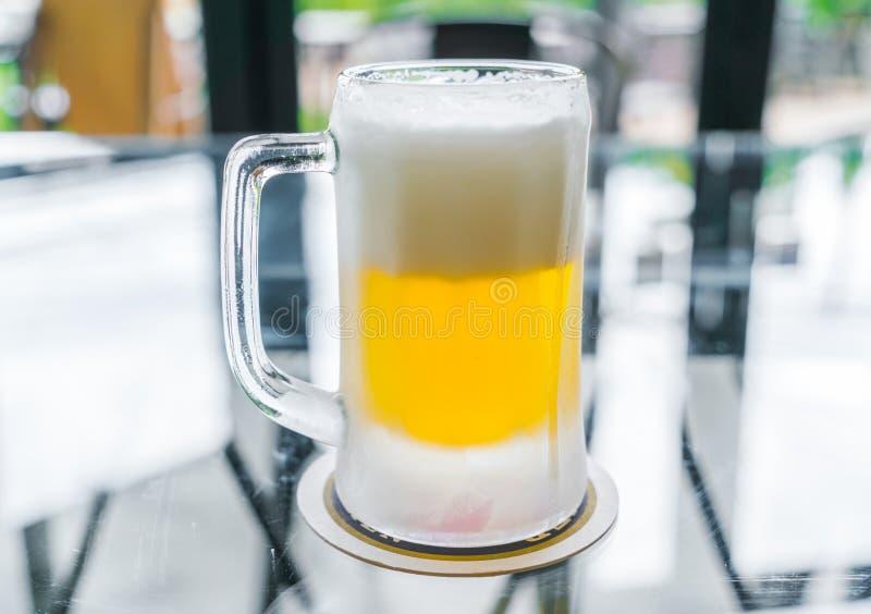 Becher mit Bier auf Tabelle lizenzfreies stockfoto
