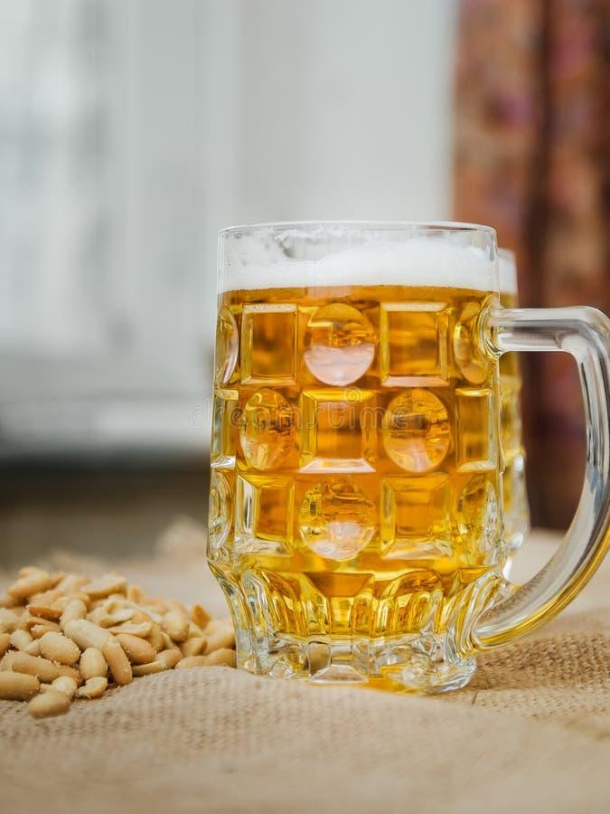 Becher mit Bier und gesalzenen Erdnüssen auf dem Tisch lizenzfreies stockfoto