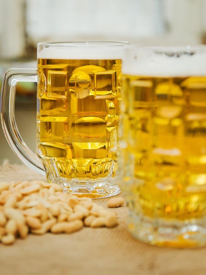 Becher mit Bier und gesalzenen Erdnüssen auf dem Tisch lizenzfreie stockfotos