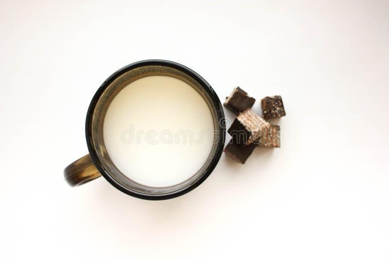 Becher mit Milch und Bonbon stockfoto
