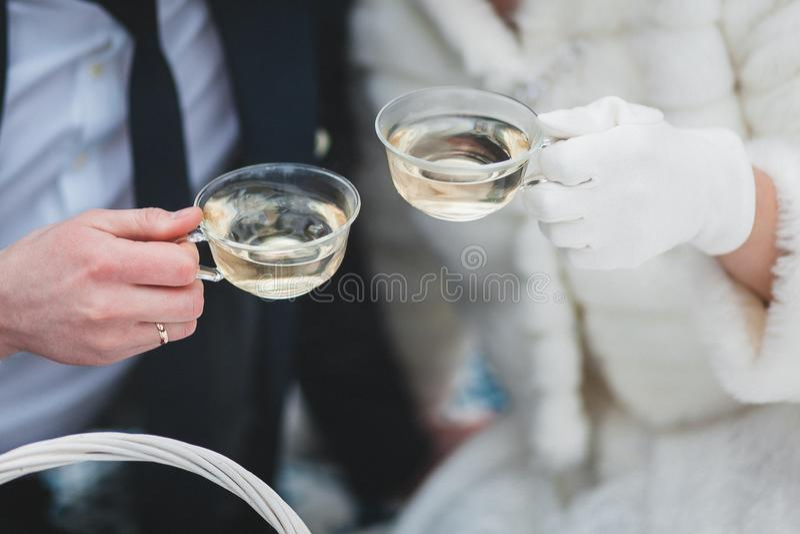 Becher mit Tee in den Händen der Braut und des Bräutigams im Winter lizenzfreies stockfoto