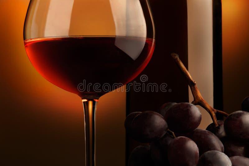Becher Rotwein mit Flasche und Weintraube lizenzfreie stockfotos
