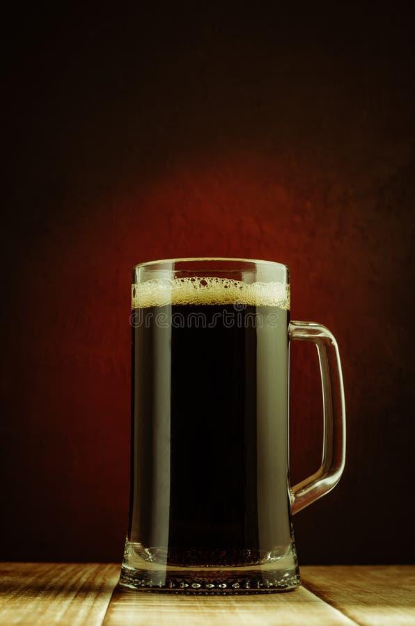 Becher voll des Bieres/des Bechers voll Bieres auf einem Holztisch und einem roten Hintergrund lizenzfreies stockbild