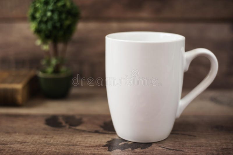 Bechermodell Kaffeetasseschablone Kaffeetasse-Druckdesign-Schablone Weißes Becher-Modell, altes Buch und Blume, hölzerner Hinterg lizenzfreie stockbilder