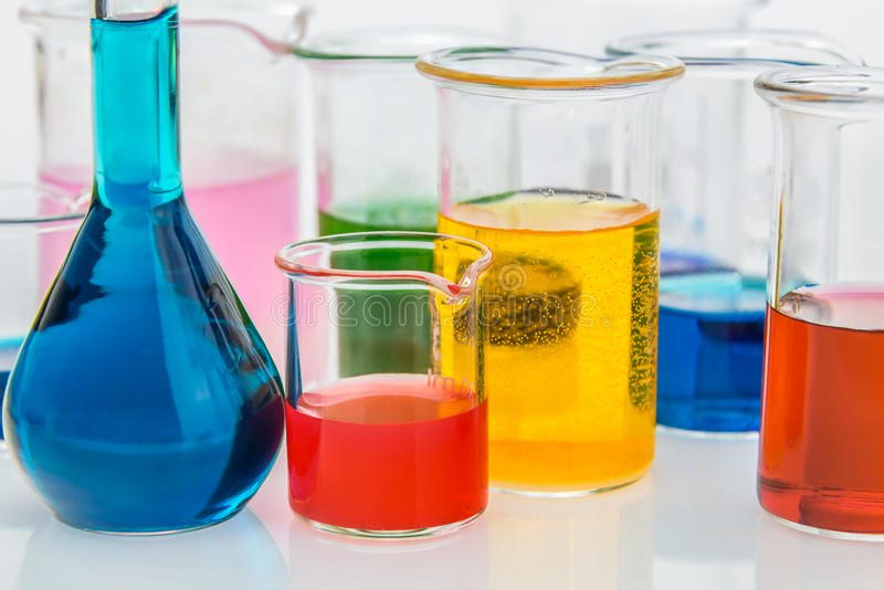 Bechers avec différents types d'indicateurs dans les acides et la base photos libres de droits