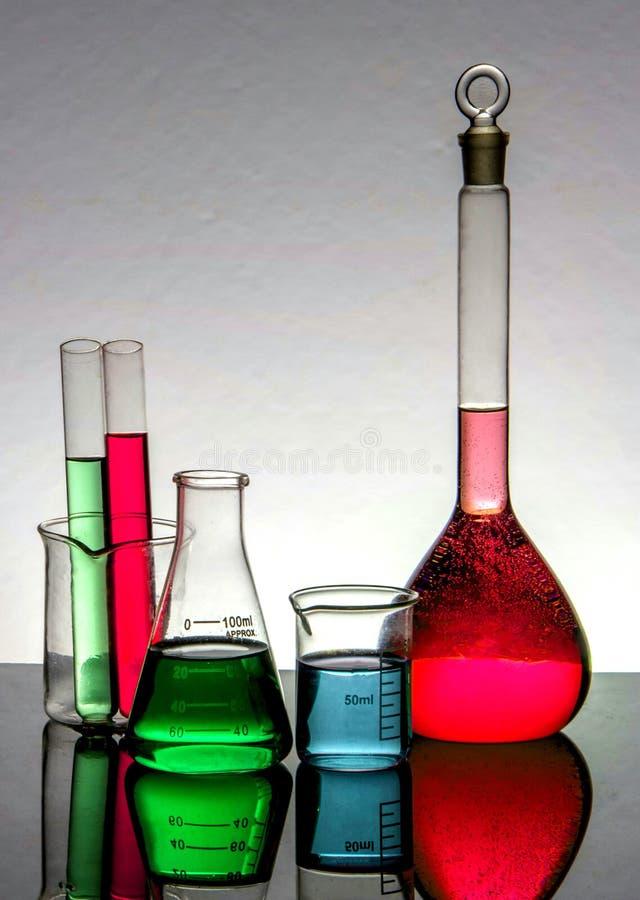 Bechers de laboratoire de chimie, et tubes à essai sur refléter le fond de table extérieure et périodique image stock