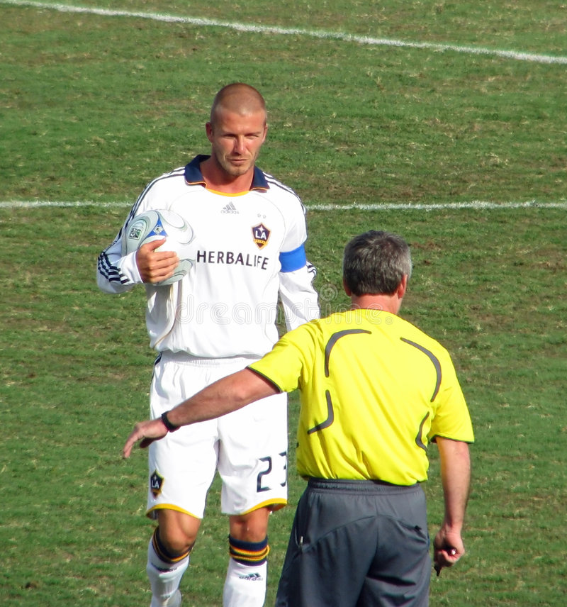 Beckham and Referee. LA Galaxy soccer player and captain David Beckham. Beckham holds and soccer ball as he walks toward the referee in a game against the FC stock photos