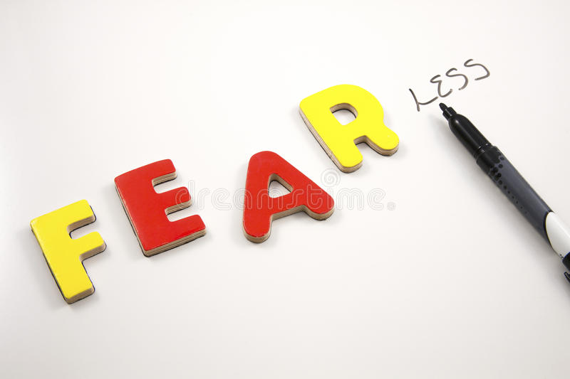 Becoming Fearless. The word FEAR becoming FEARLESS on a whiteboard royalty free stock image