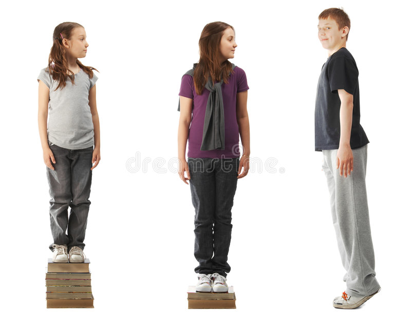 Becoming wise. Two smaller girls standing on a pile of books and a boy standing on tiptoe royalty free stock photos