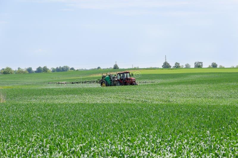 Becs de tracteur fertilisant le champ de cultures image libre de droits