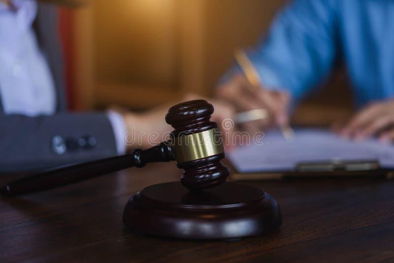 Bedöma auktionsklubban på träteable bakgrund med advokaten och attorne arkivfoton