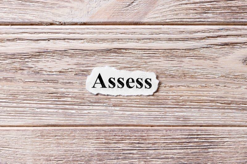 BEDÖMA av ordet på papper Begrepp Ord av ASSESS på en träbakgrund royaltyfri foto