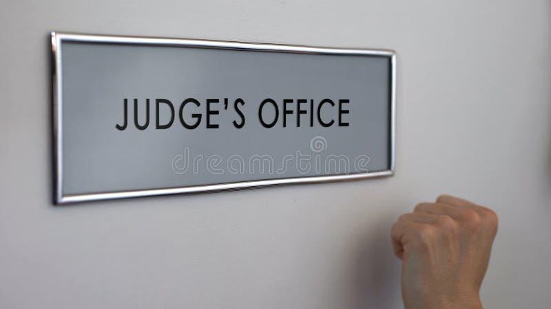 Bedöma kontorsdörren, advokathanden som knackar closeupen, domstolsförhandling, rättsligt system royaltyfri fotografi