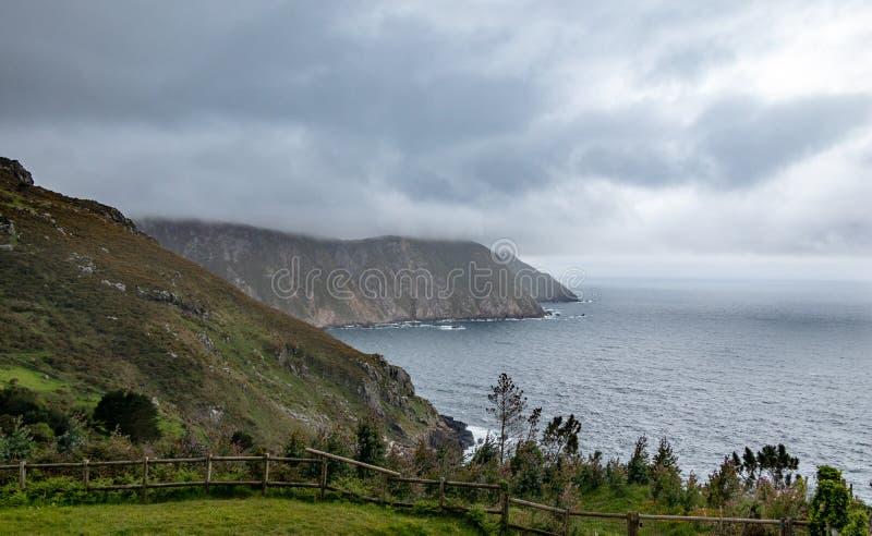 Bed?va atlantiska klippor p? norrkusten av Galicia, Spanien Betar och skogar som v?nder mot havet, tr?staket royaltyfri foto