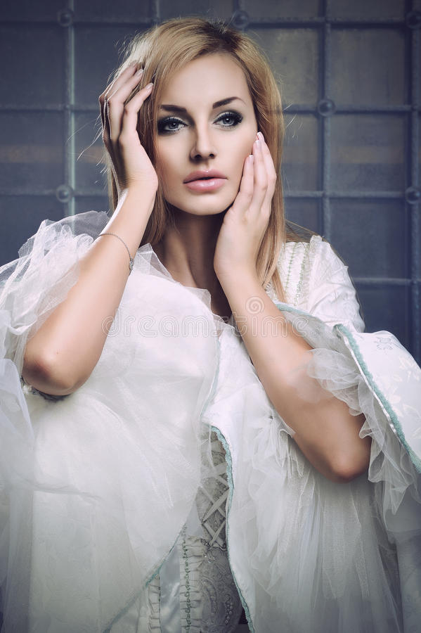 Bedöva blond skönhet som ha på sig tappningklänningen royaltyfria bilder