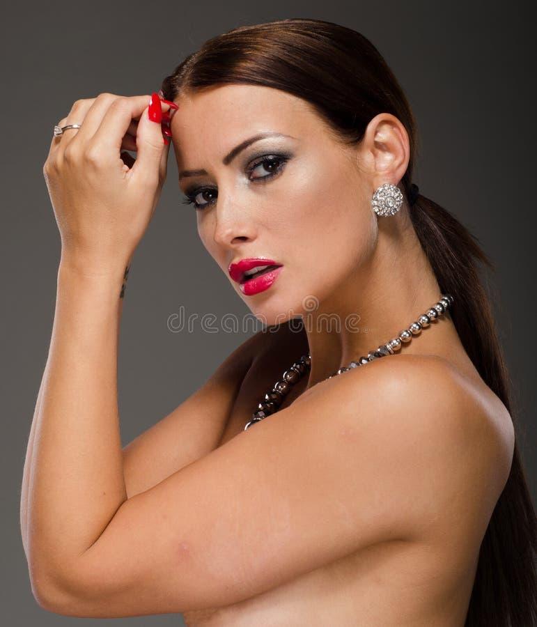 Bedöva brunett med händer på hennes framsida royaltyfria bilder