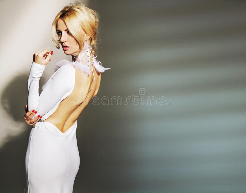 Bedöva den bärande vita kappan för ung kvinna royaltyfri bild