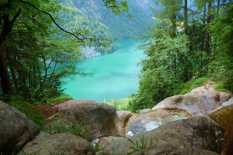 Bedöva den färgrika vattenfallet som faller till Konigsee som är bekant som djupast Tyskland` s och den mest rena sjön som lokali royaltyfria foton