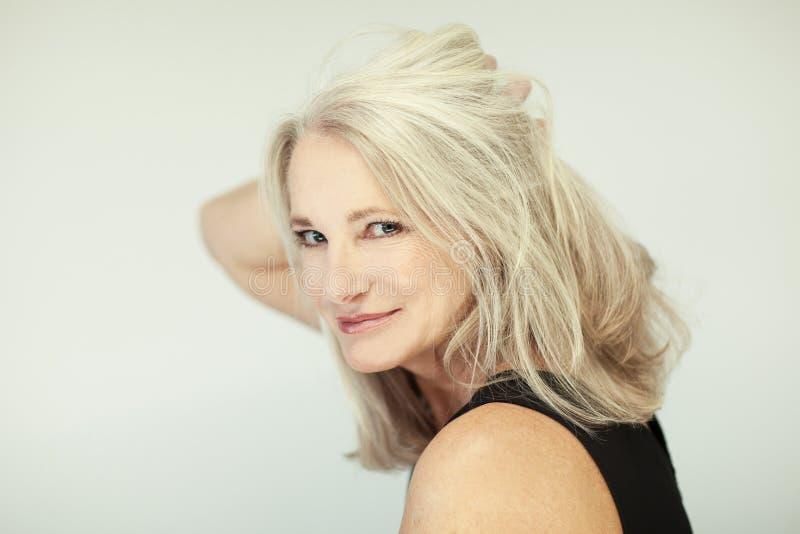 Bedöva den härliga och självsäkra bästa åldriga kvinnan med grått hår som ler in i kamera royaltyfria foton