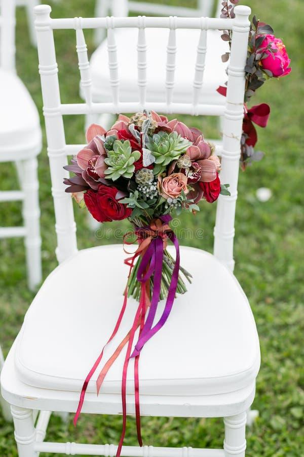 Bedöva den röda brud- buketten på vit stol bröllop för brudceremoniblomma Blandning av suckulenter, orkidér och rosor arkivbild