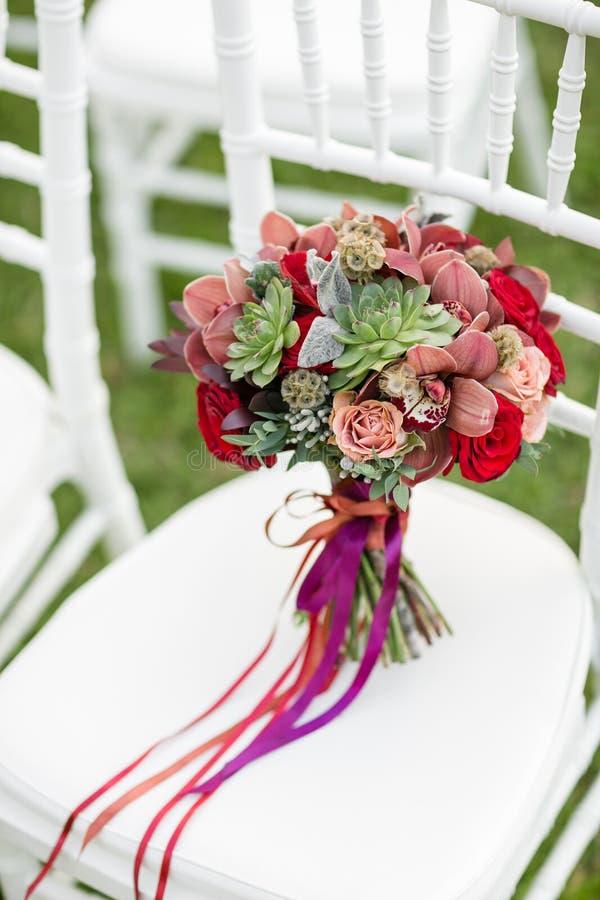 Bedöva den röda brud- buketten på vit stol bröllop för brudceremoniblomma Blandning av suckulenter, orkidér och rosor royaltyfri fotografi