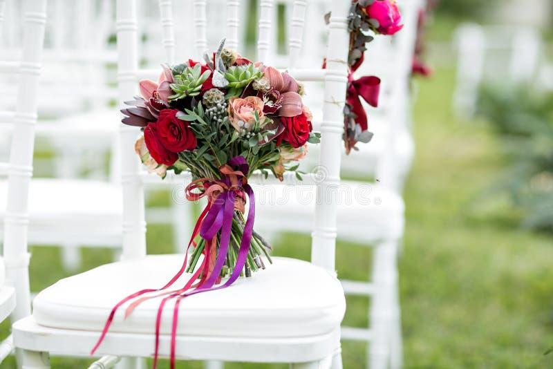 Bedöva den röda brud- buketten på vit stol bröllop för brudceremoniblomma Blandning av suckulenter, orkidér och rosor arkivfoto