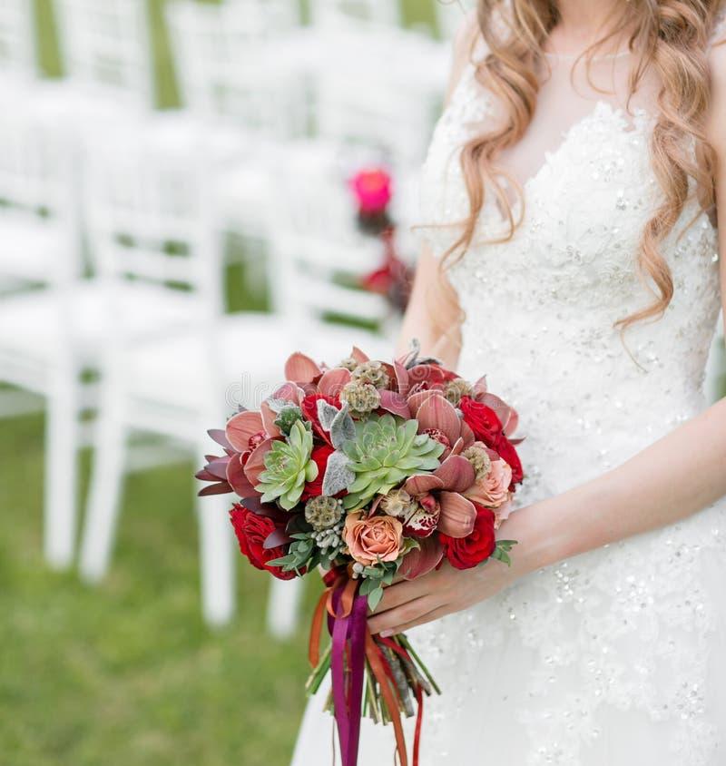 Bedöva den röda brud- buketten på vit stol bröllop för brudceremoniblomma Blandning av suckulenter, orkidér och rosor royaltyfria foton