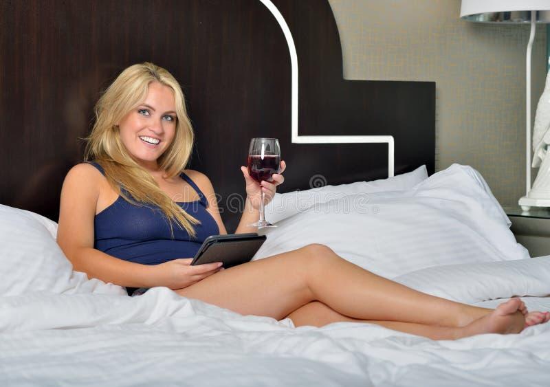 Bedöva den unga blonda kvinnan med vin och e-avläsaren royaltyfria bilder