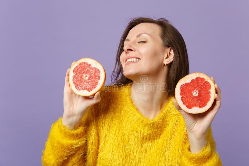 Bedöva den unga kvinnan i pälströjan som håller ögon stängda rymma halfs av den nya mogna grapefrukten som isoleras på violett pa arkivbild