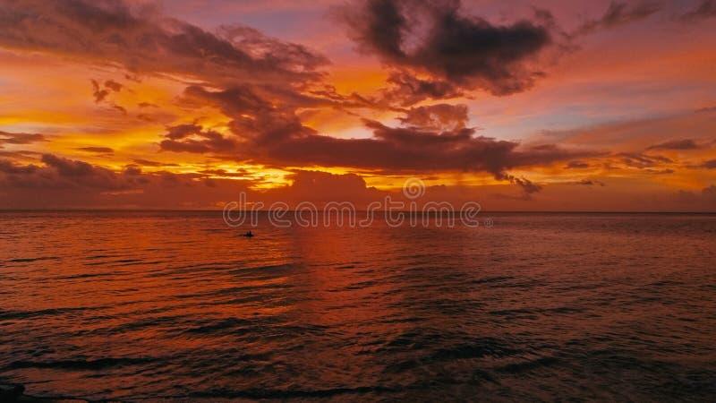 Bedöva härlig flyg- surrbild av en röd tropisk solnedgång ovanför havshavet med man två i ett kanotfiske arkivbilder