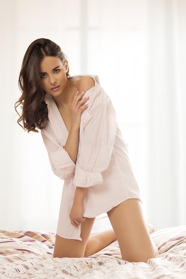Bedöva kvinnan posera in på säng royaltyfri foto