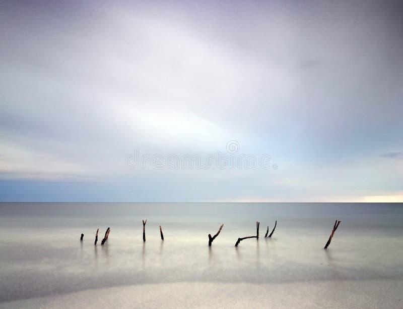 Bedöva lång landsdcape för exponeringssuddighetssoluppgång av den idylliska stranden fotografering för bildbyråer