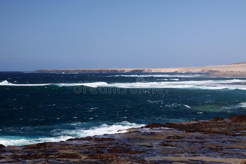 Bedöva naturlig synvinkel med kala torra kullar, turkoslagun och det rasande lösa havet på den nordvästliga kusten av Fuerteventu royaltyfri bild