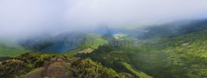 Bedöva panoramautsikt på vulkaniska sjöar Gröna Lagoa de Santiago och blåa Lagoa Azul med den Sete Cidades byn royaltyfri bild