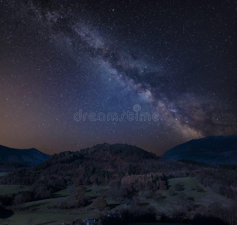 Bedöva sammansatt bild för vibrerande Vintergatan över Catbells nära Derwentwater i sjöområdet med livliga nedgångfärger lite var arkivfoton
