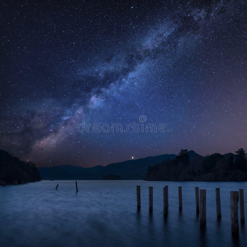 Bedöva sammansatt landskapbild för vibrerande Vintergatan över Derwent vatten i sjöområde under Autumn Fall soluppgång med mjukt fotografering för bildbyråer