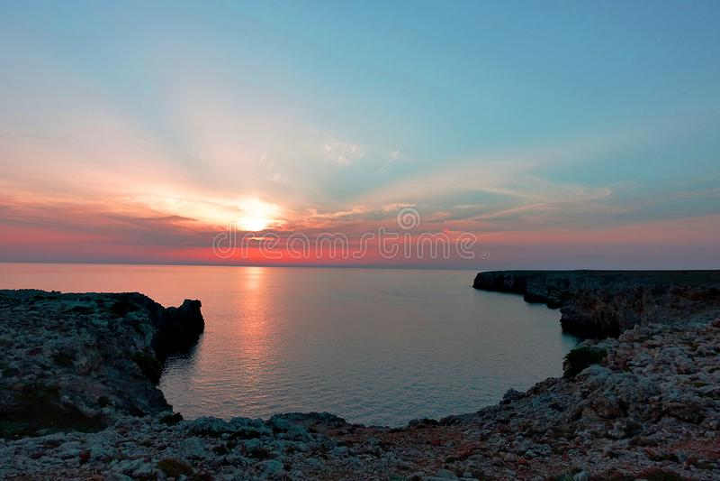 Bedöva sikt under solnedgången på den steniga klippan i havet på menorca arkivbilder